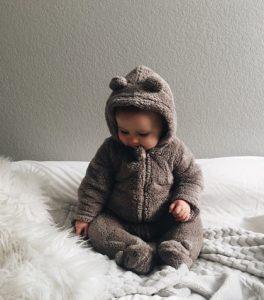 baby sidder på seng med teddy-dragt